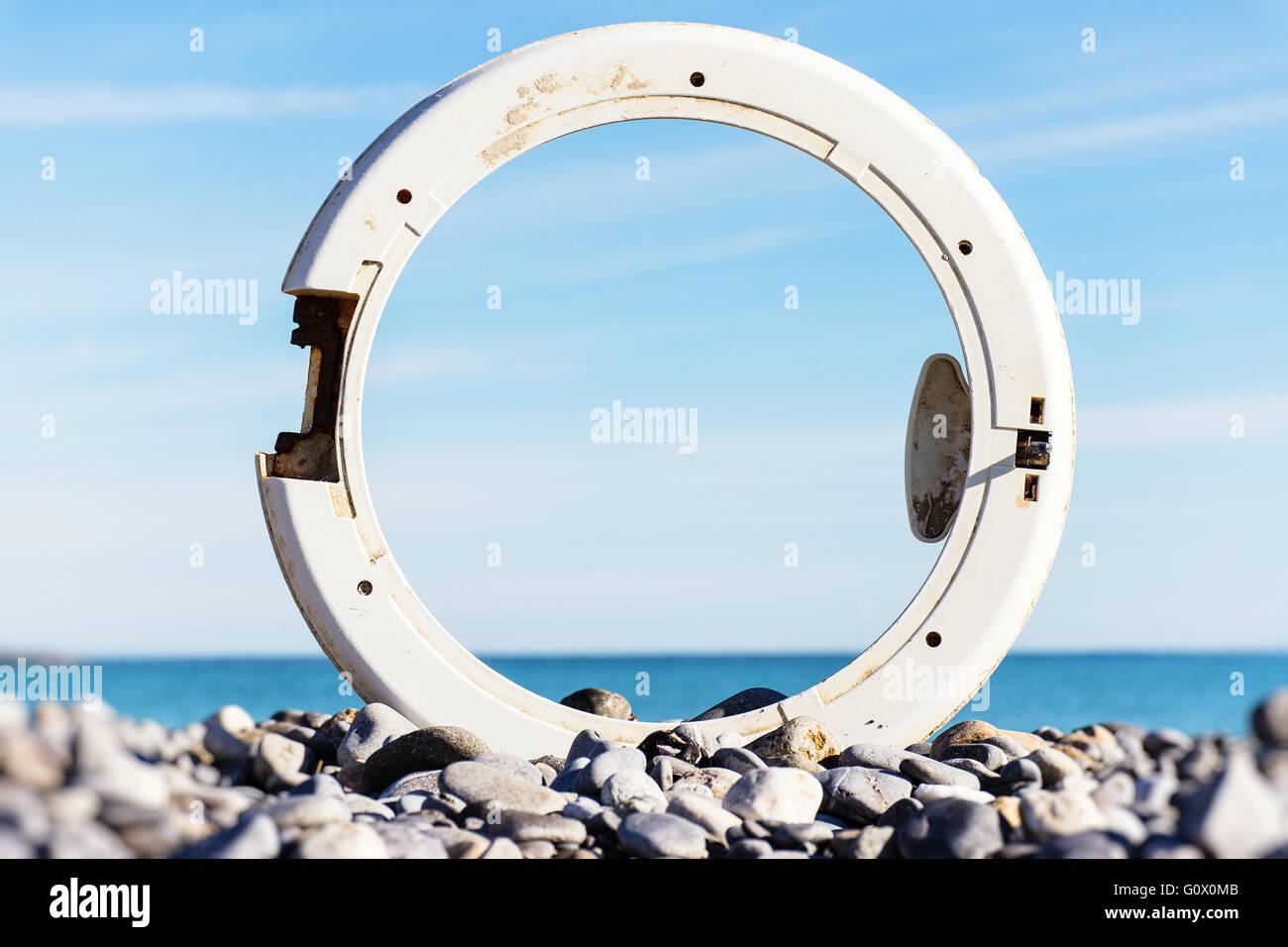 portholes, washing machine, beach, trash - Stock Image