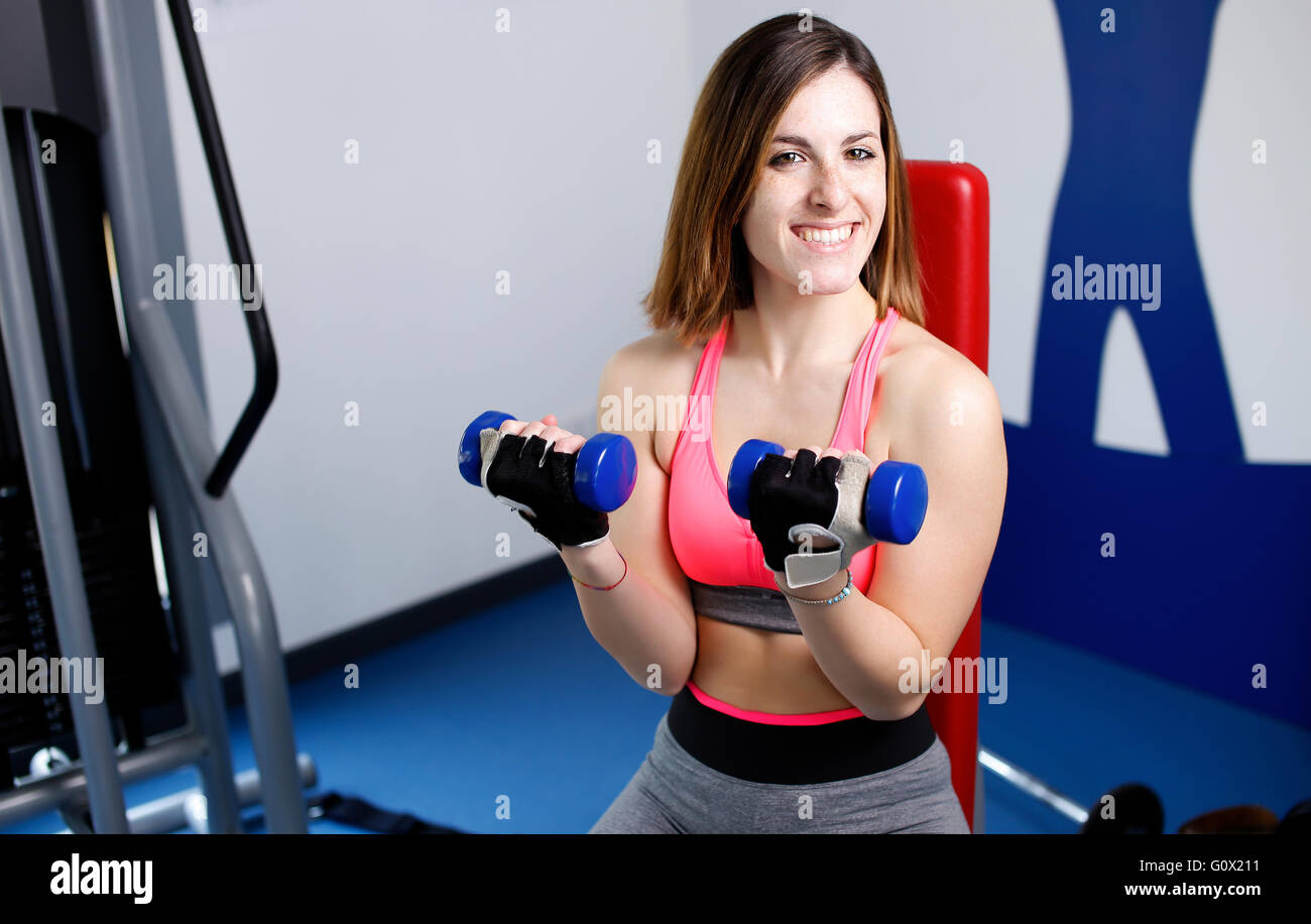 Strong woman weightlifting at the gym looking happy Stock Photo