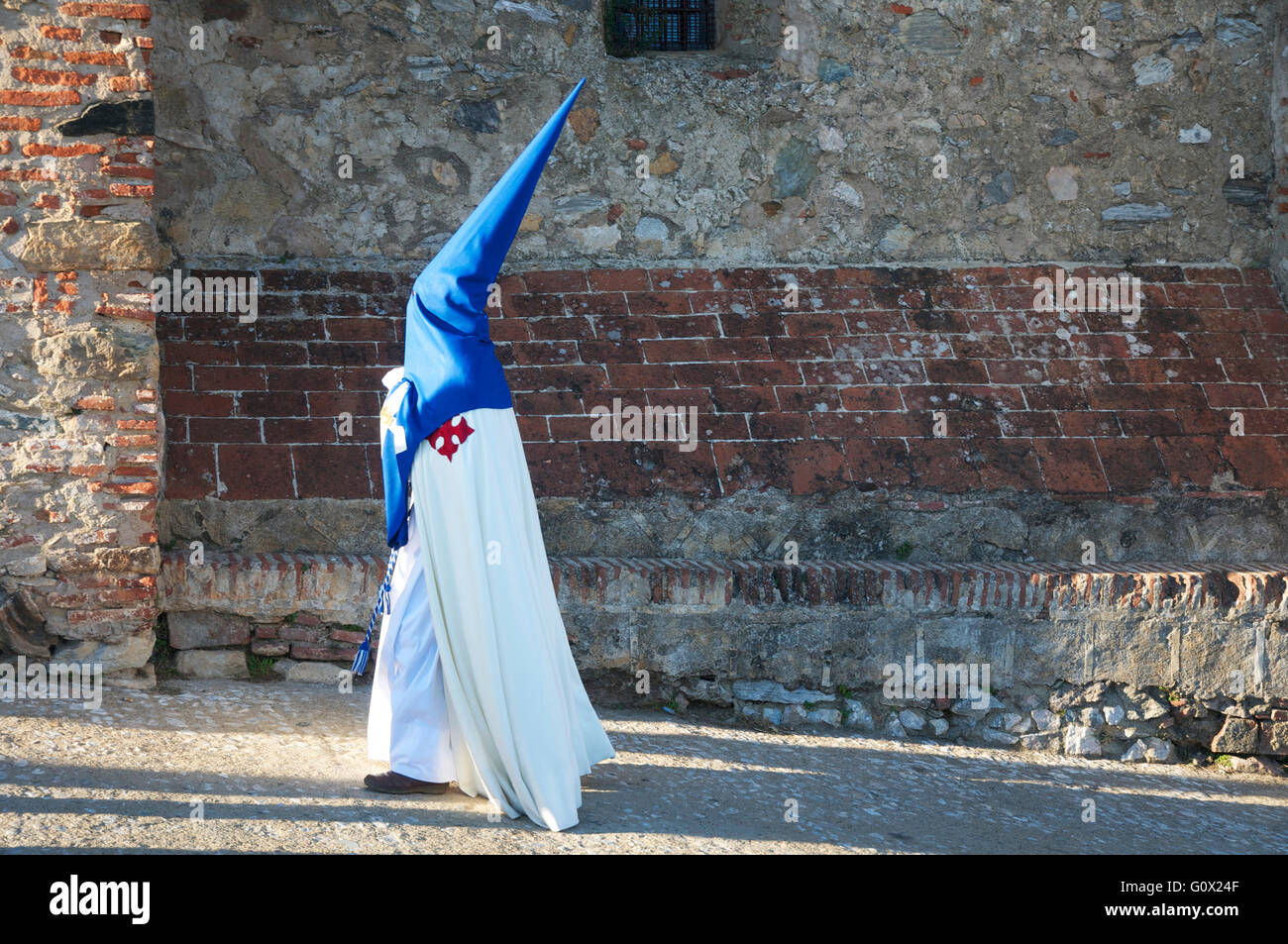 Penitents gathering for Semana Santa parade from church back into town. - Stock Image
