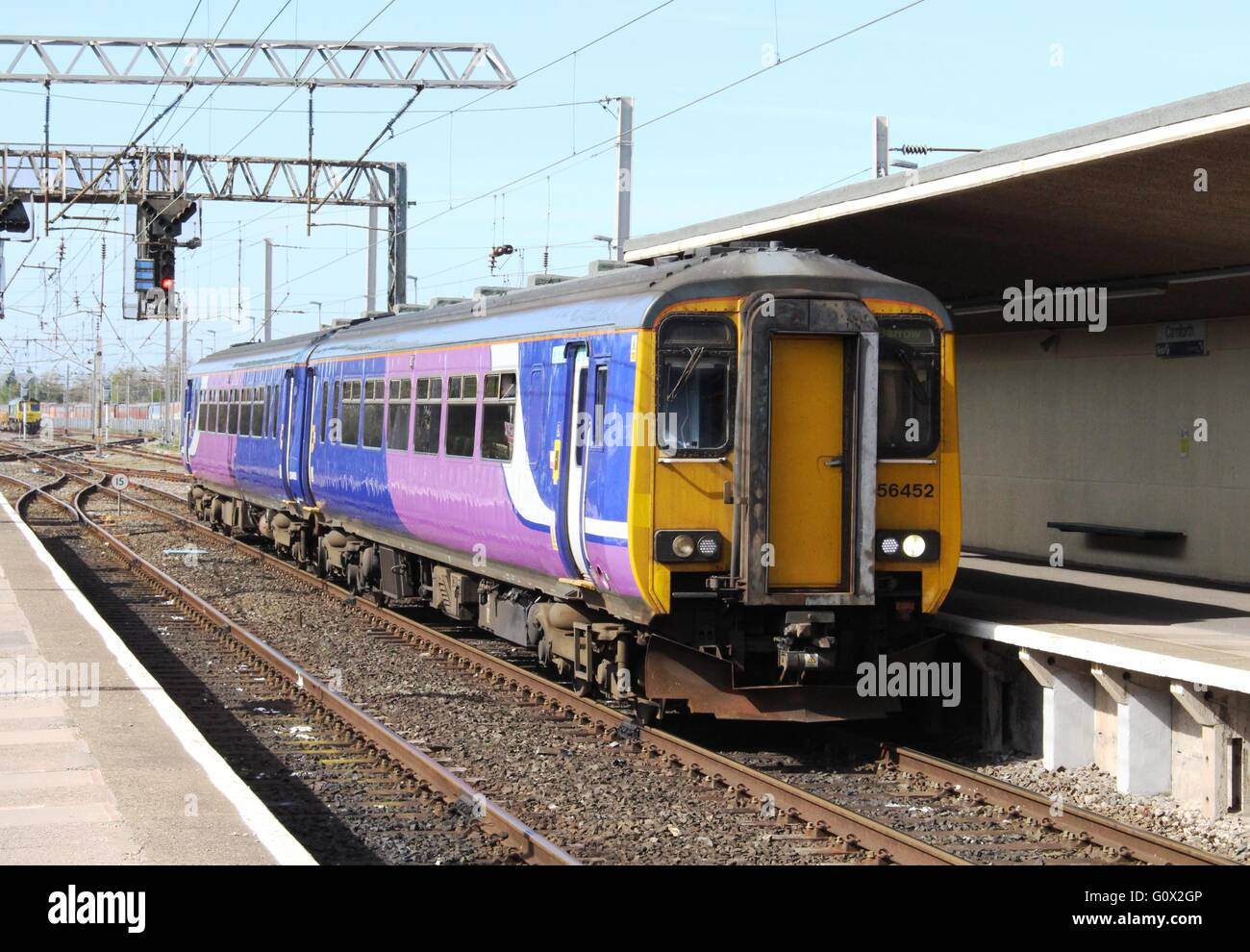 Class 156 diesel multiple unit 156452, in Northern livery without the Northern branding arriving at Carnforth station. - Stock Image