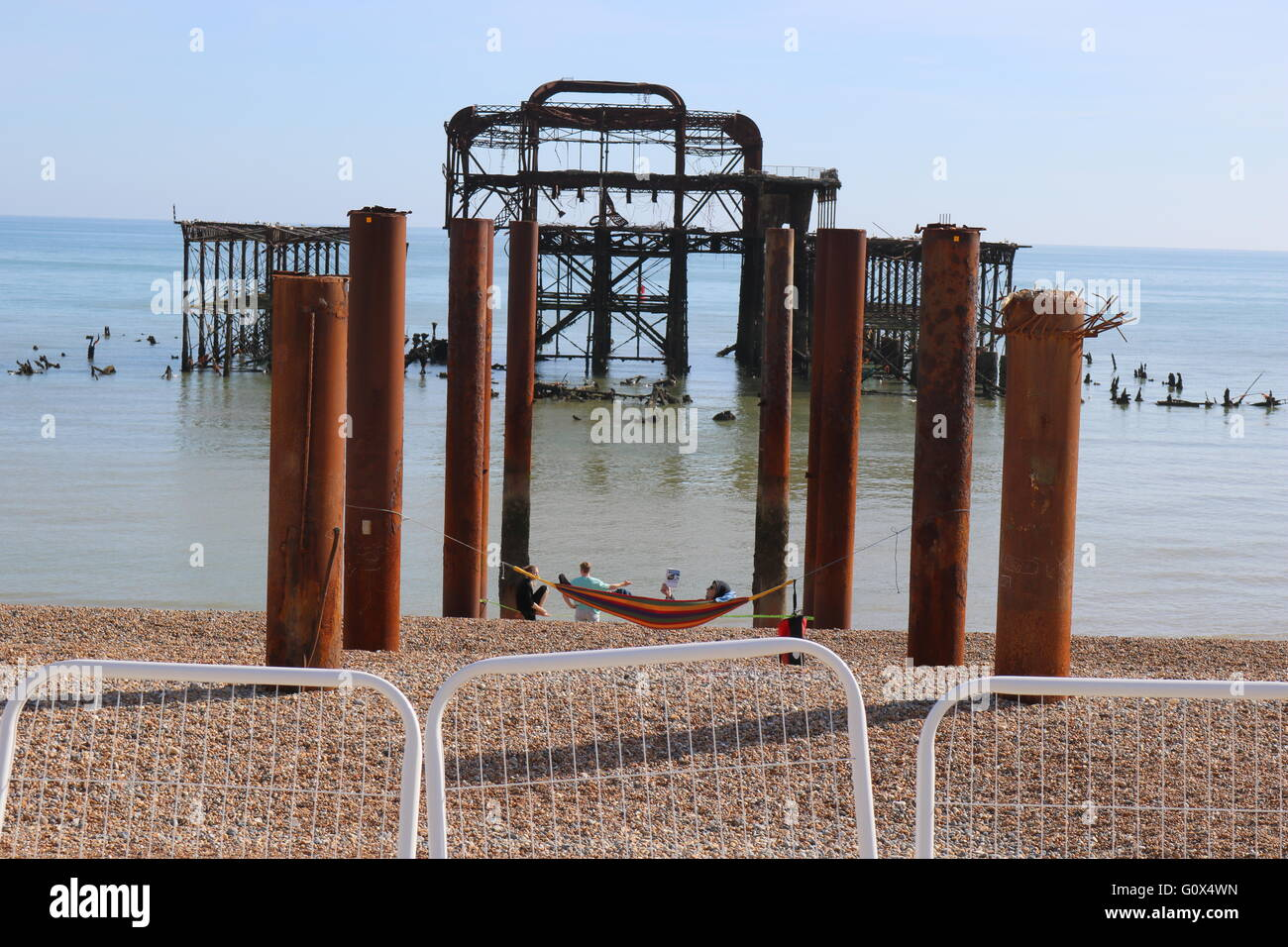 A sunbather rests on a hammock supported on the old posts from the burnt down remains of Brighton West Pier. - Stock Image