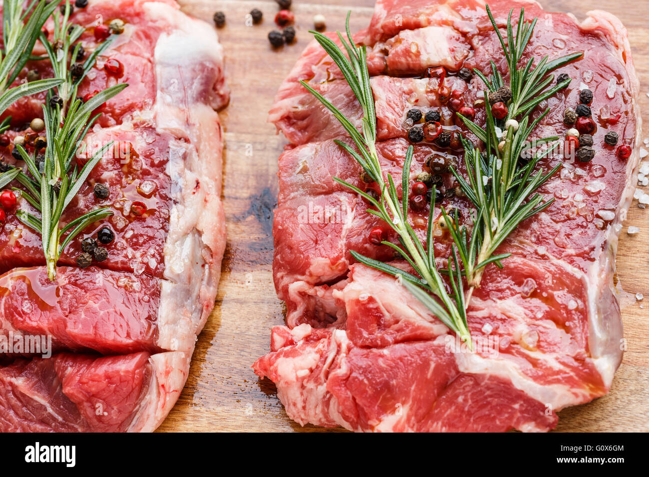 Raw Beef Steaks, salt, pepper, rosemary  on cutting board - Stock Image