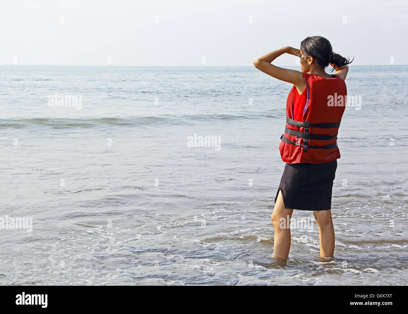 Teen girl in life jacket waiting at the beach in Goa, India, ready for water sport activities - Stock Image