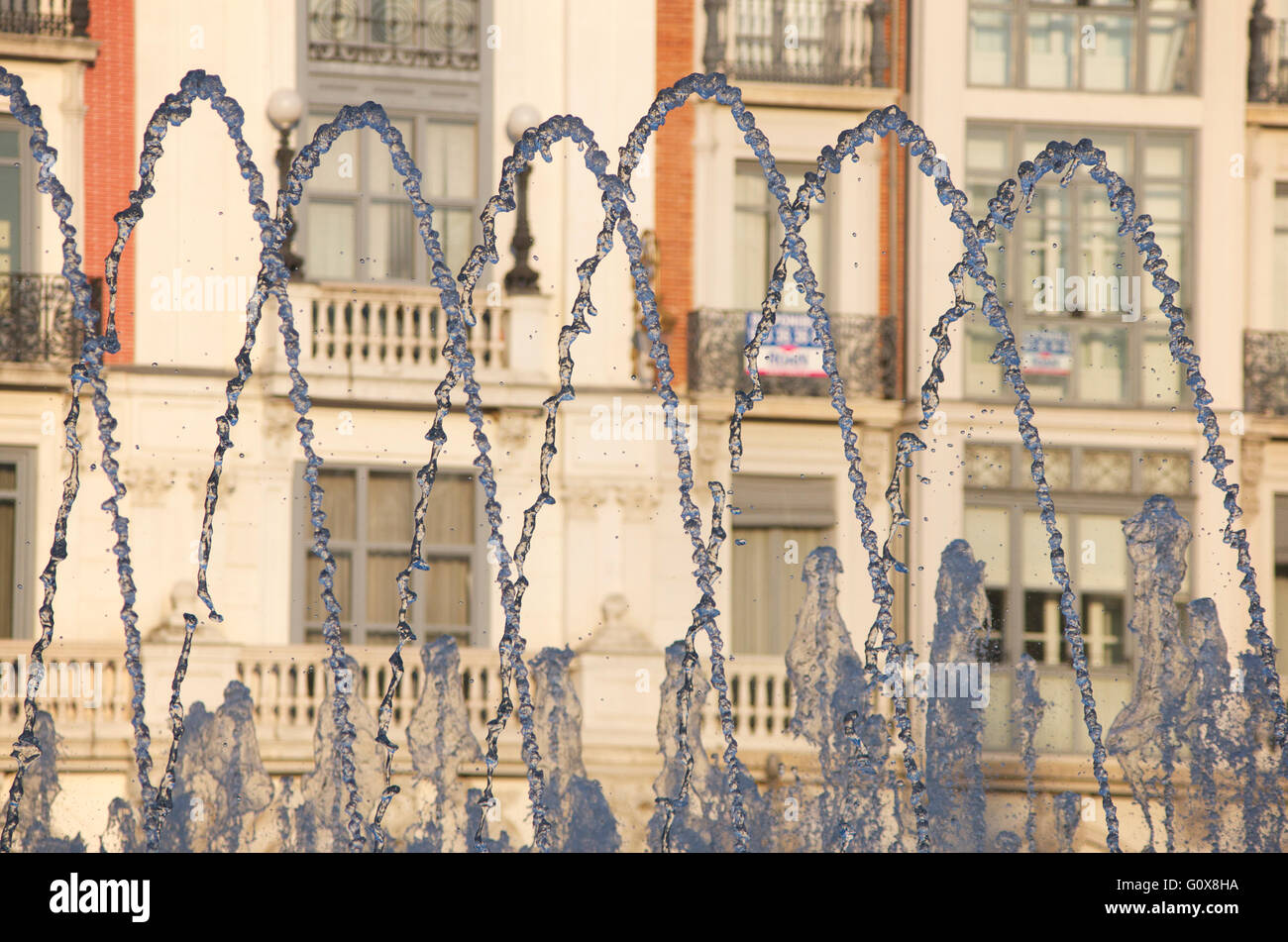 Water jets spurting from a fountain against city building background, Valladolid, Spain - Stock Image