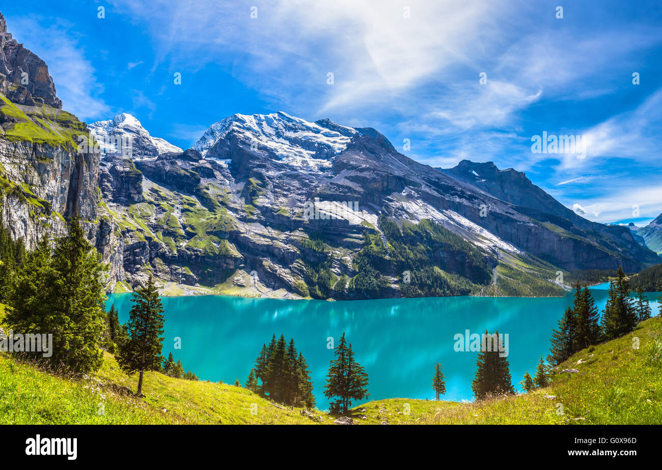 The panorama in summer view over the Oeschinensee (Oeschinen lake) and the alps on the other side near Kandersteg - Stock Image