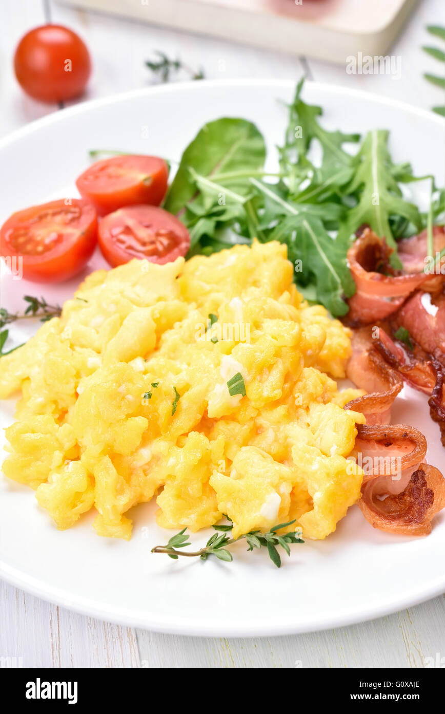 Breakfast with scrambled eggs, bacon and vegetable salad - Stock Image