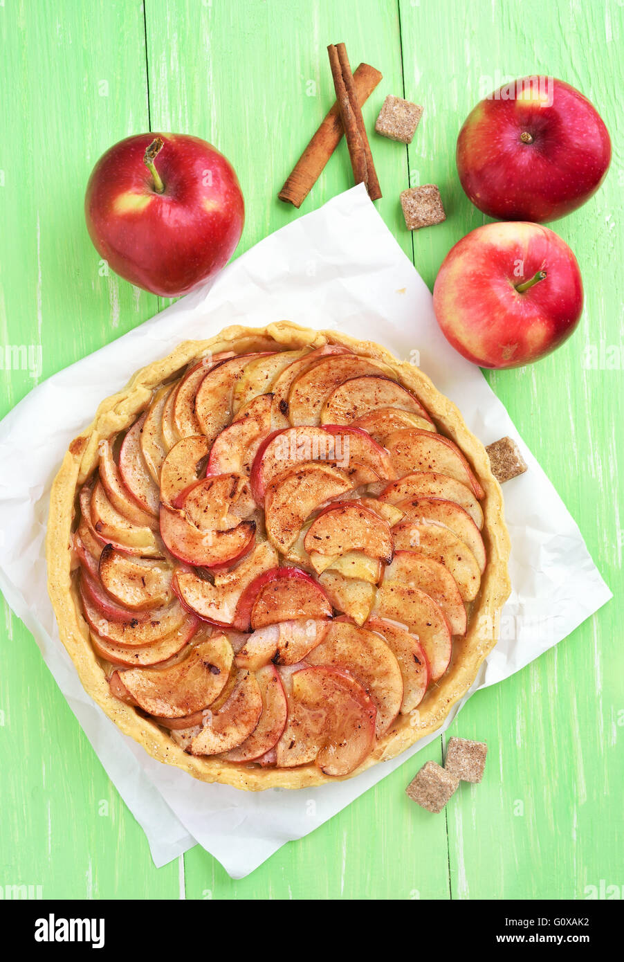 Apple pie on green wooden table, top view - Stock Image