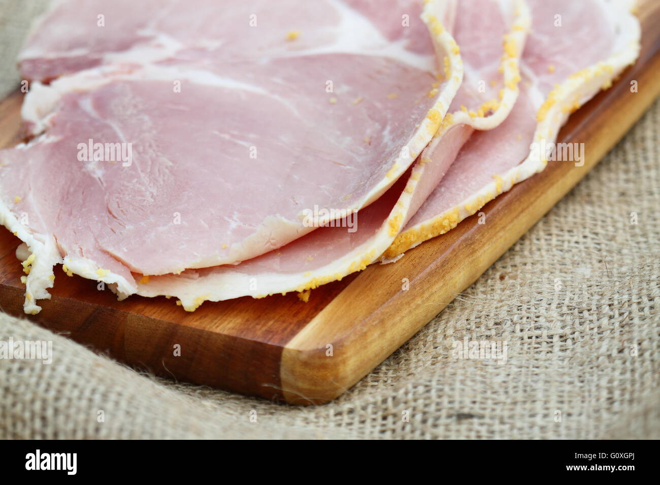 Ham slices wooden chopping board - Stock Image