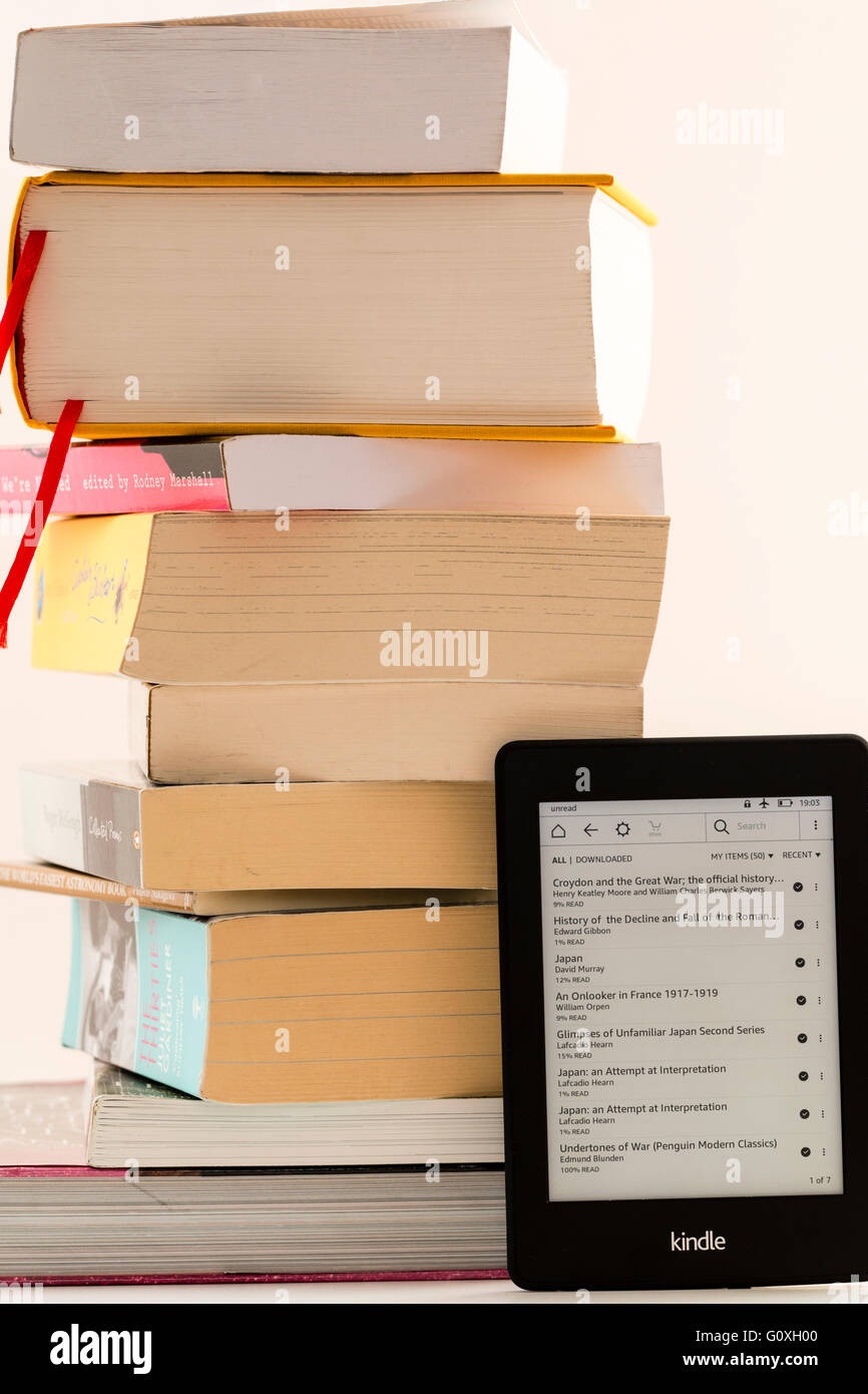 Amazon Kindle turned on leaning against stack of paperback books to