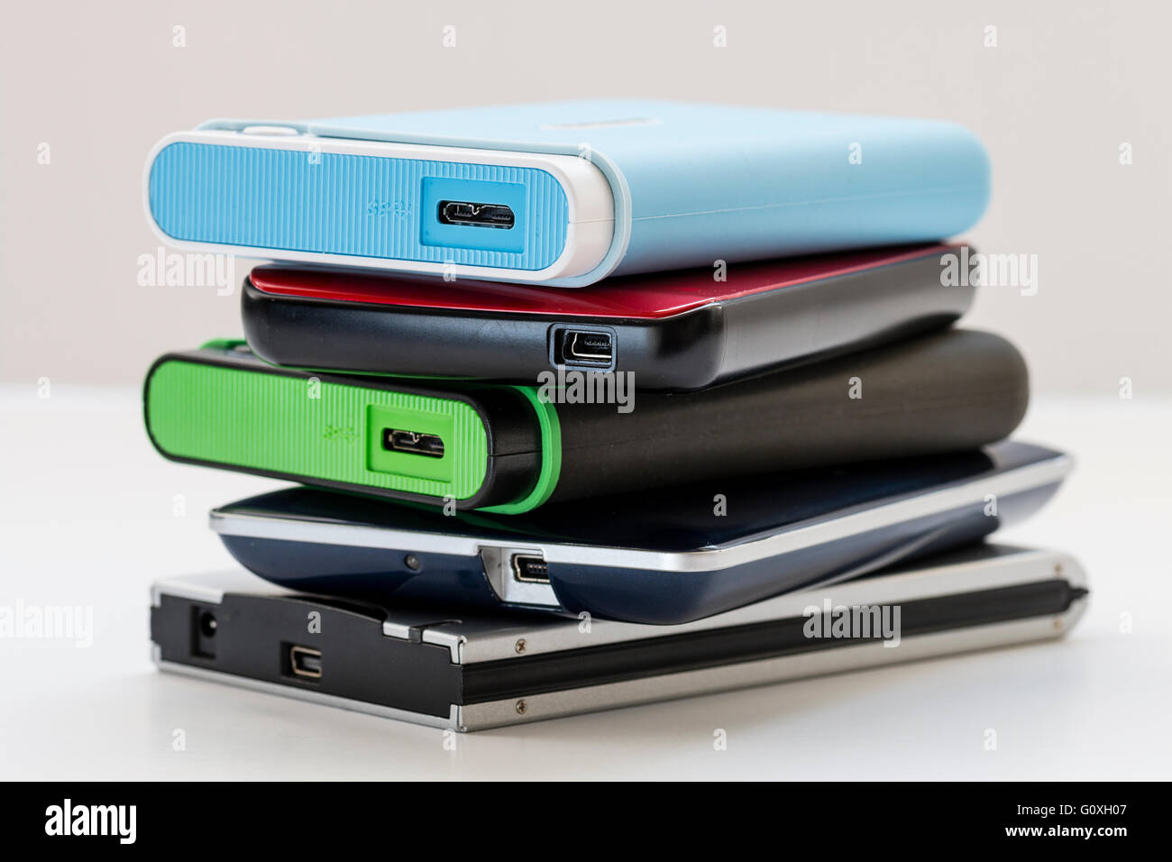 Five different and various coloured external portable hard drivers stacked up showing end with USB connection points. Stock Photo