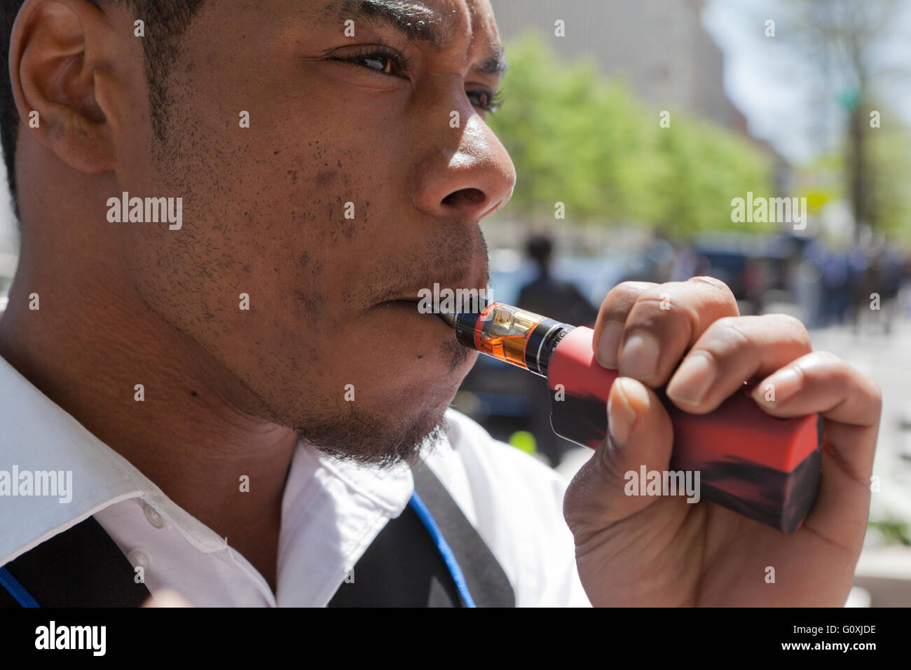 Young African-American man using an e-cigarette - USA - Stock Image