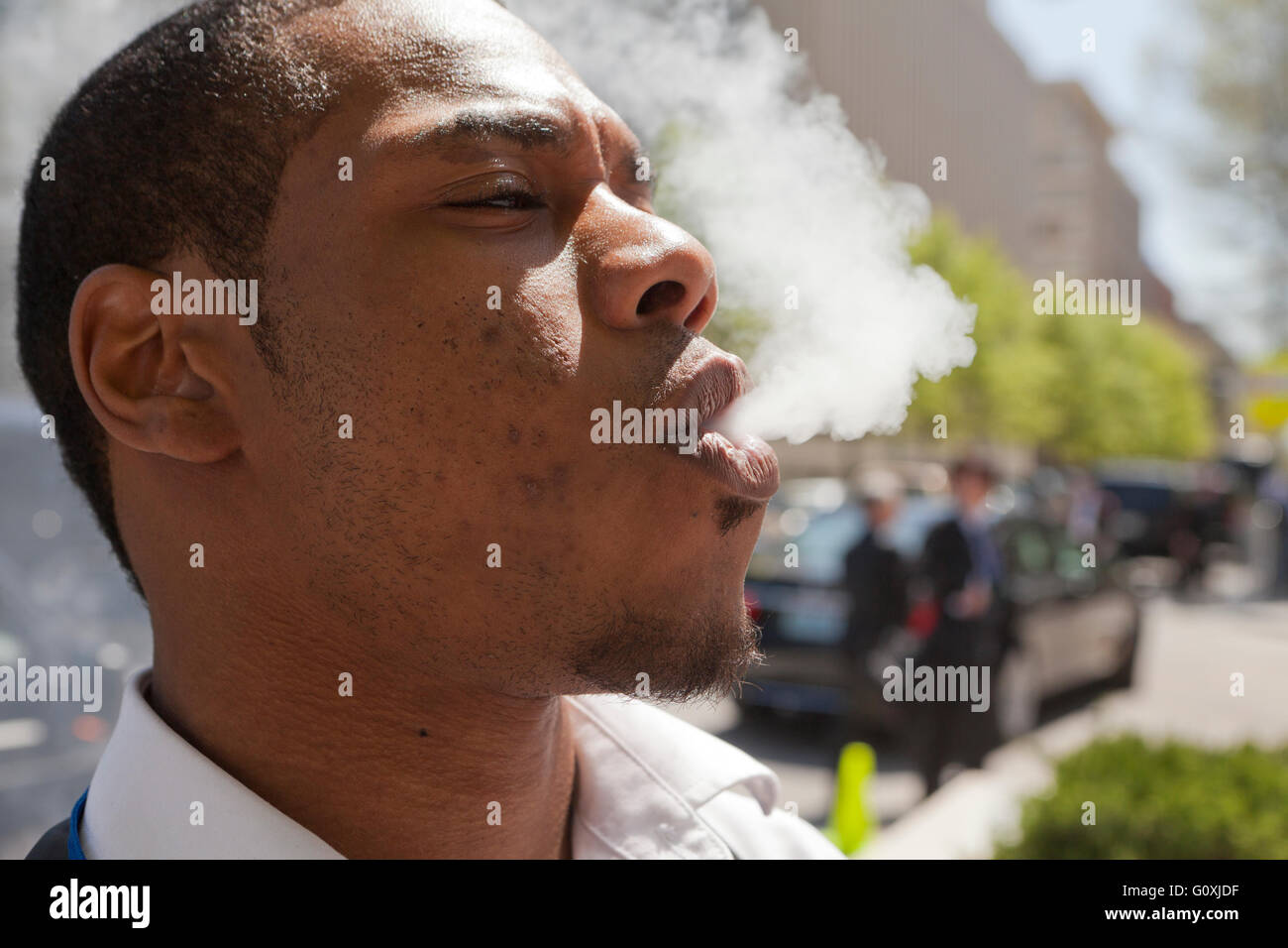 Young African-American man blowing vapor - USA - Stock Image