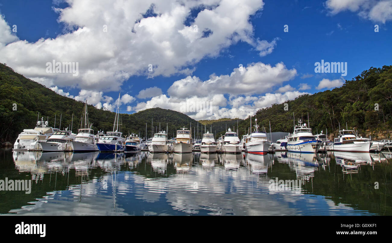 Luxury cruisers rest in their berths in Bobbin Head Marina on the Hawkesbury River. - Stock Image