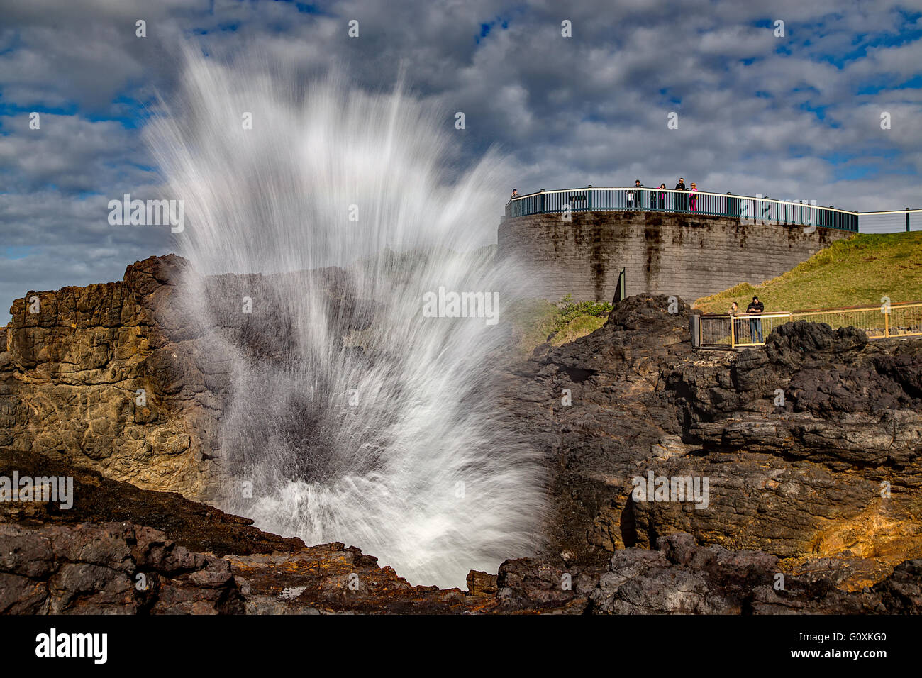 Tourists watch as the famous Kiama Blowhole erupts. - Stock Image