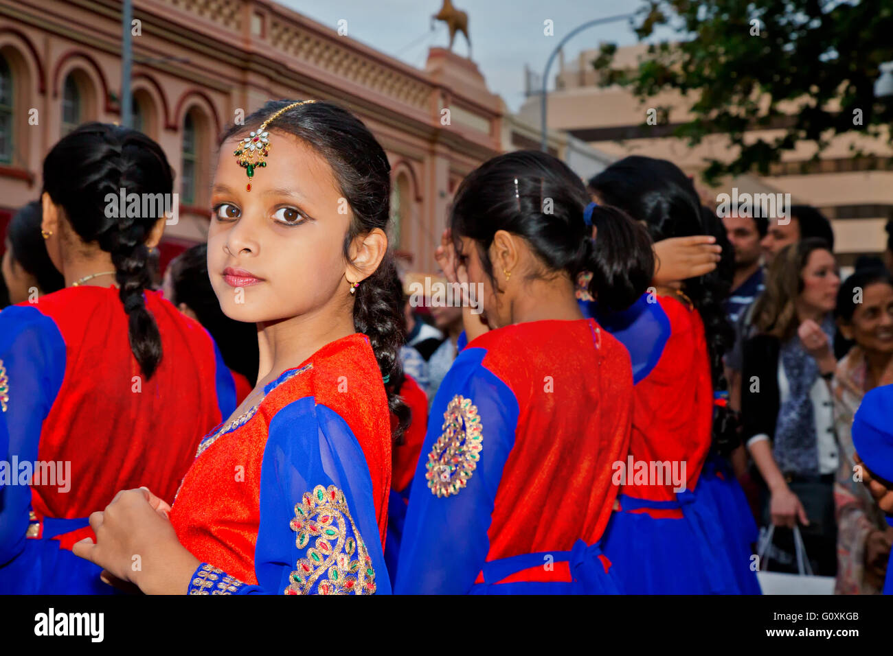 A young girl dancer wears a traditional Indian costume in a parade. - Stock Image