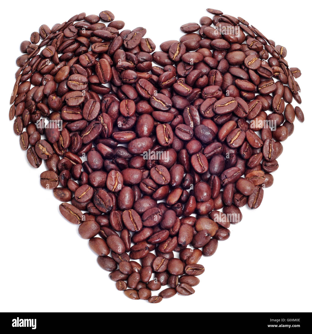 a pile roasted coffee beans forming a heart on a black background - Stock Image