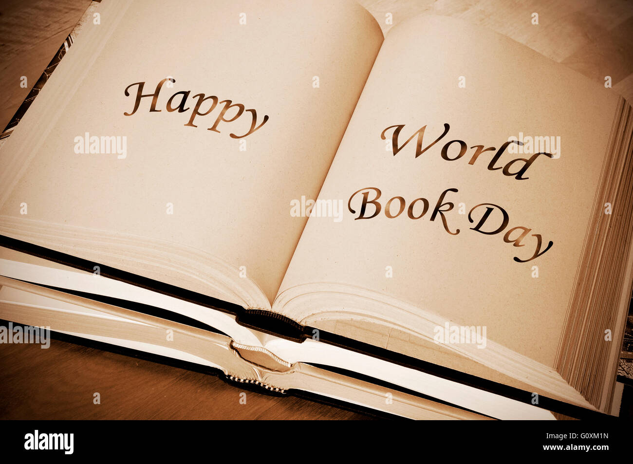 sentence happy world book day, celebrated each year on april 23, written on an open book - Stock Image