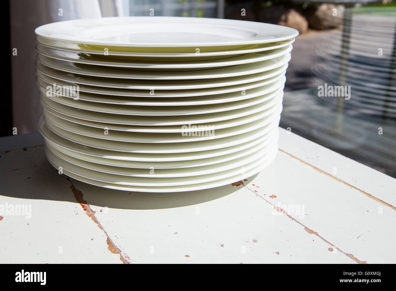 White plates piled on vintage table close to window - Stock Image