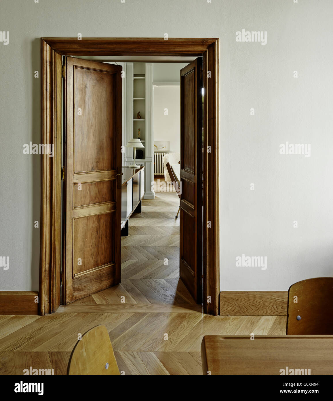 Partial view of a living room through an opened door with parquet flooring and a retro side table with table l&. & Partial view of a living room through an opened door with parquet ...
