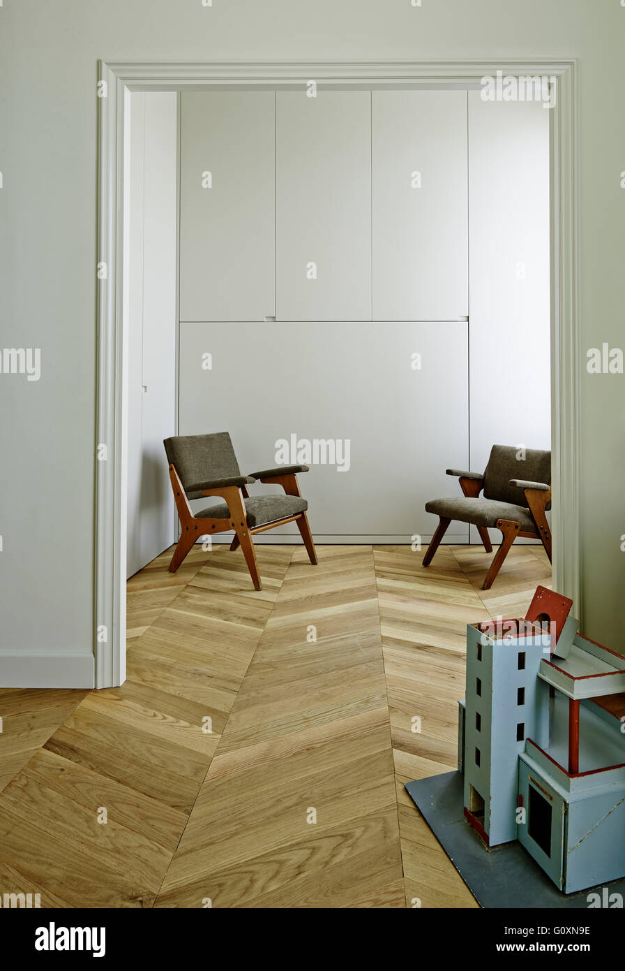 MA Apartment, Barcelona, Spain. Two mid-century chairs caddy cornered against white wall. Wood flooring. - Stock Image