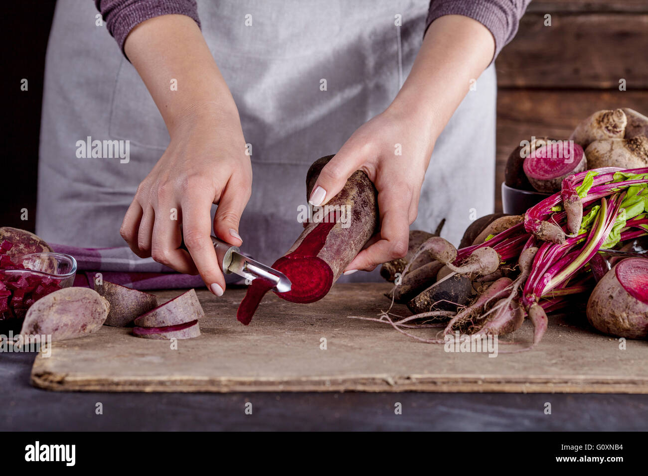 cook in gray apron is peeling a beetroot with vegetable peeler - Stock Image