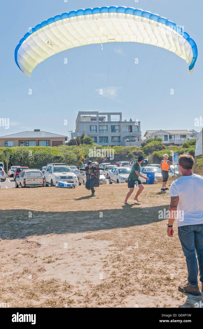 KNYSNA, SOUTH AFRICA - MARCH 3, 2016: A paraglider landing between people at a beach in Buffelsbaai (Buffalo Bay), Stock Photo