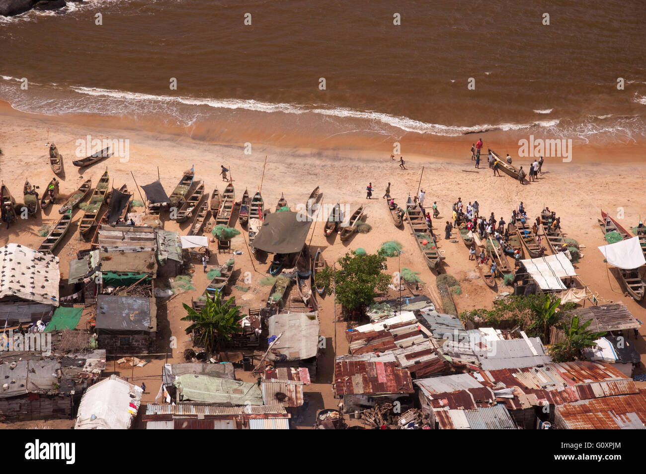 People, fishing nets and canoes make a for very interesting composition of everyday life on a beach west of Monrovia - Stock Image