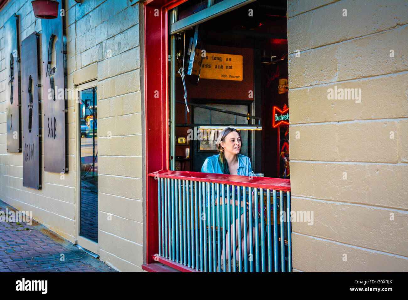 A seated young woman socializes at table along open window at the 3 Crow Bar at 5 Points district in trendy East - Stock Image