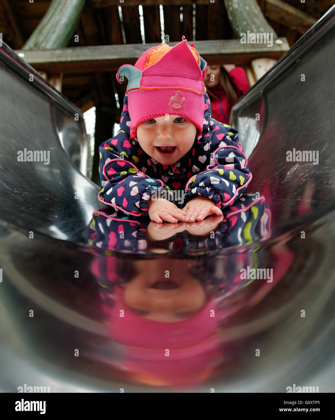 A smiling young girl (18 months old) descending a slide - Stock Image
