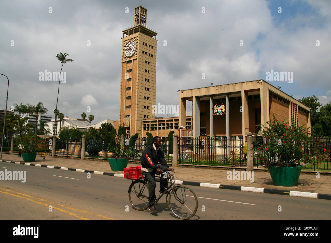 Kenyan man cycling in a bike at the center of Nairobi, with a christian church in the background - Stock Image