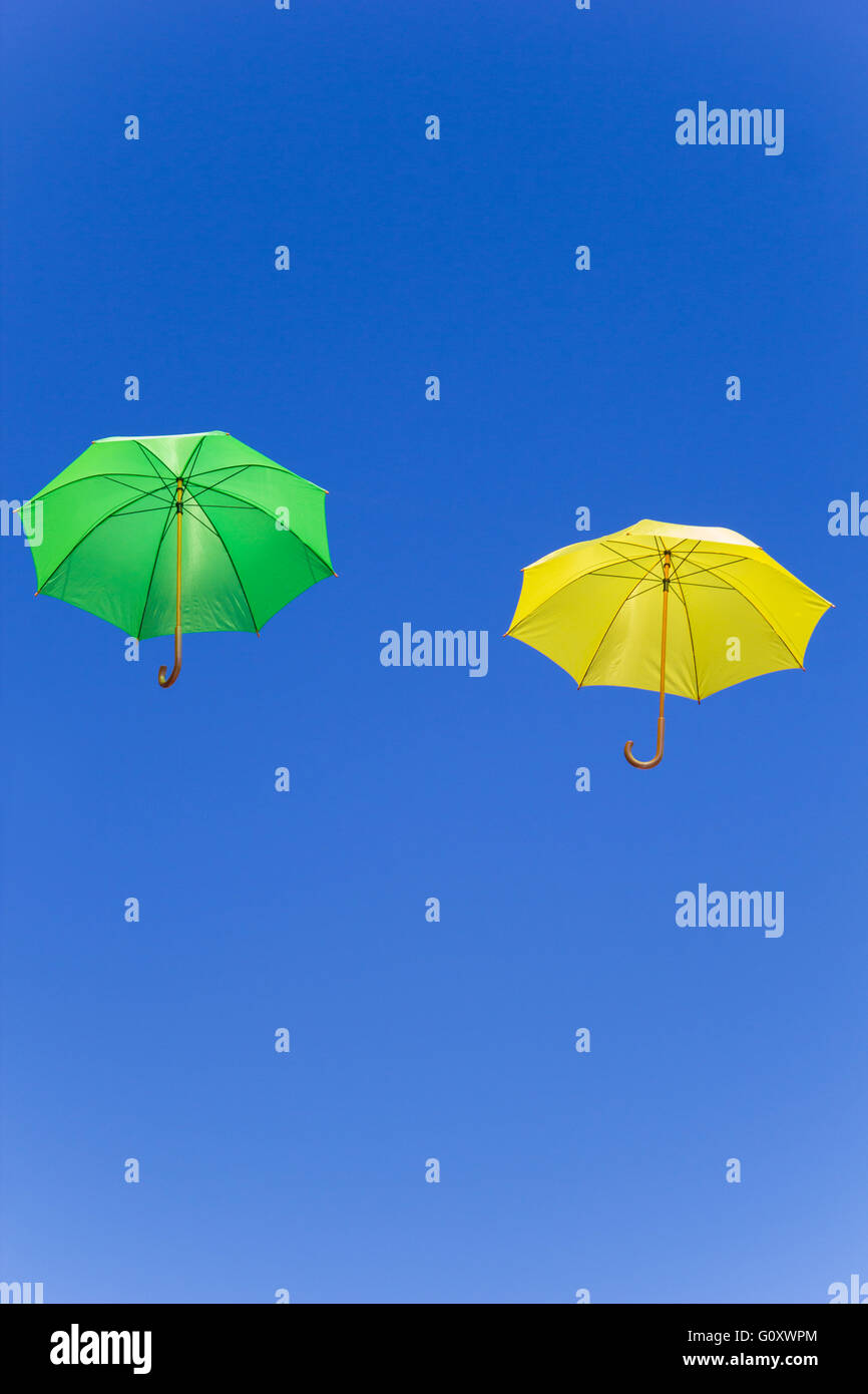 Colorful umbrellas fly in the sky on blue background - Stock Image