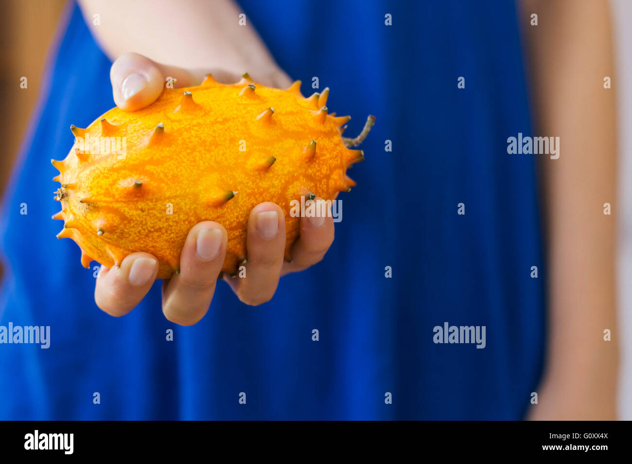 Woman holding an African Horned Melon - Stock Image