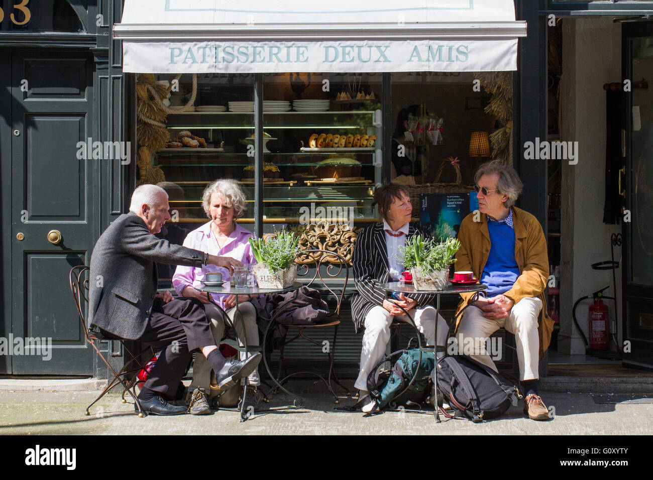 Elderly couples sitting enjoying a break at the outdoor tables of a small French café or patisserie on the - Stock Image