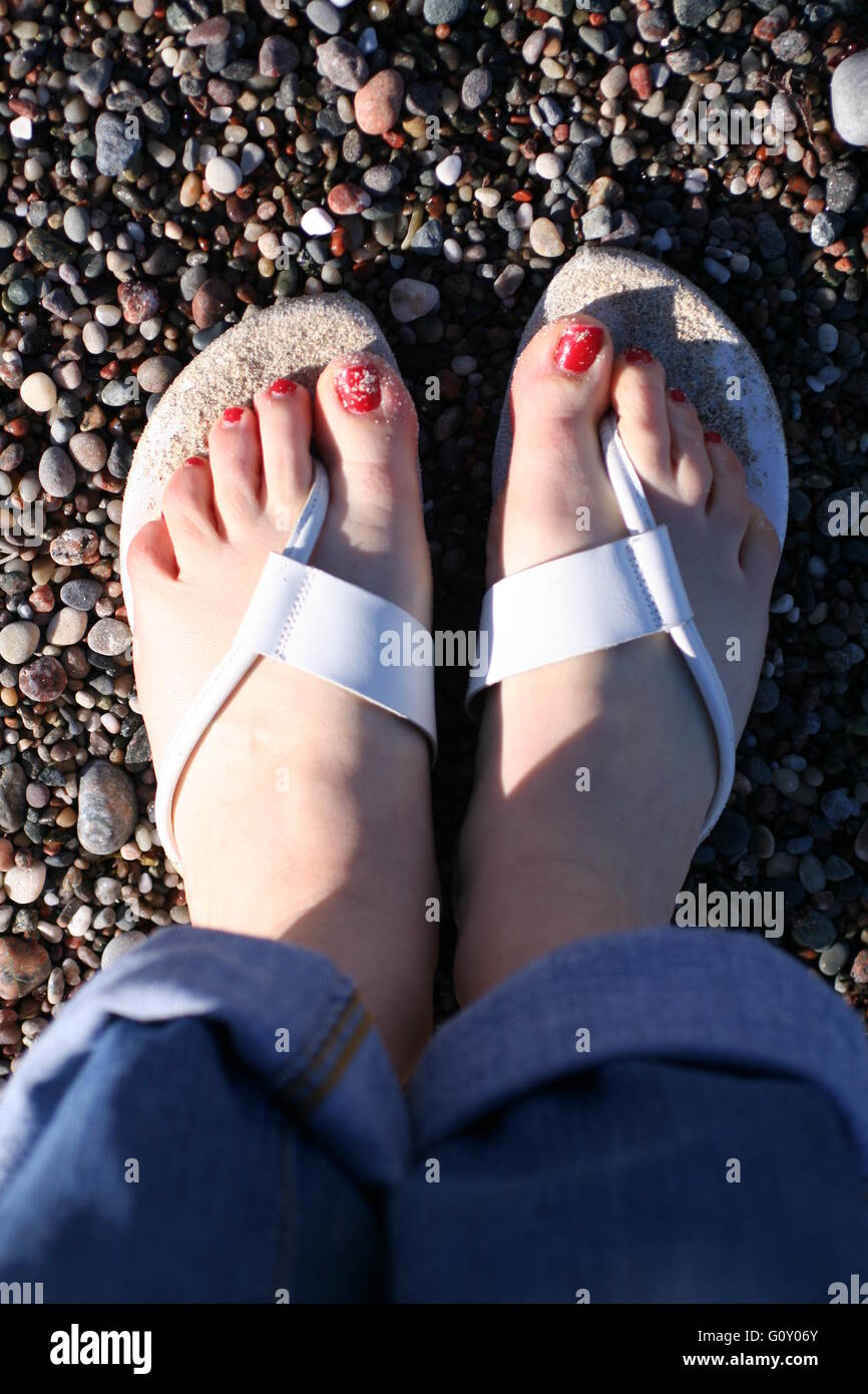Barefooted with red painted toe nails on a beach on Iona, Argyll, Scolant - Stock Image