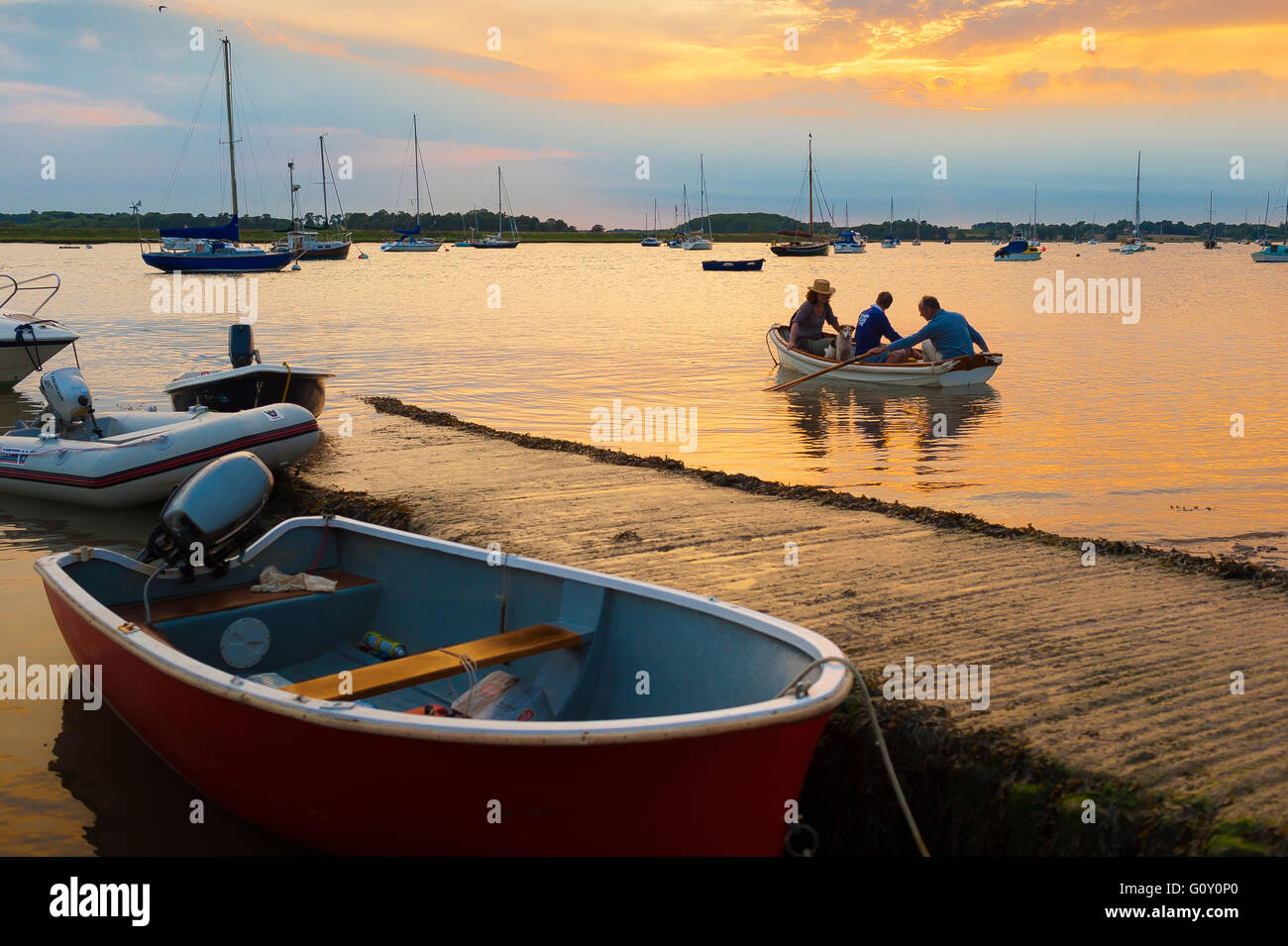 Rowing boat people sunset, view of people in a rowing boat near the wooden jetty on the River Deben in Ramsholt, - Stock Image