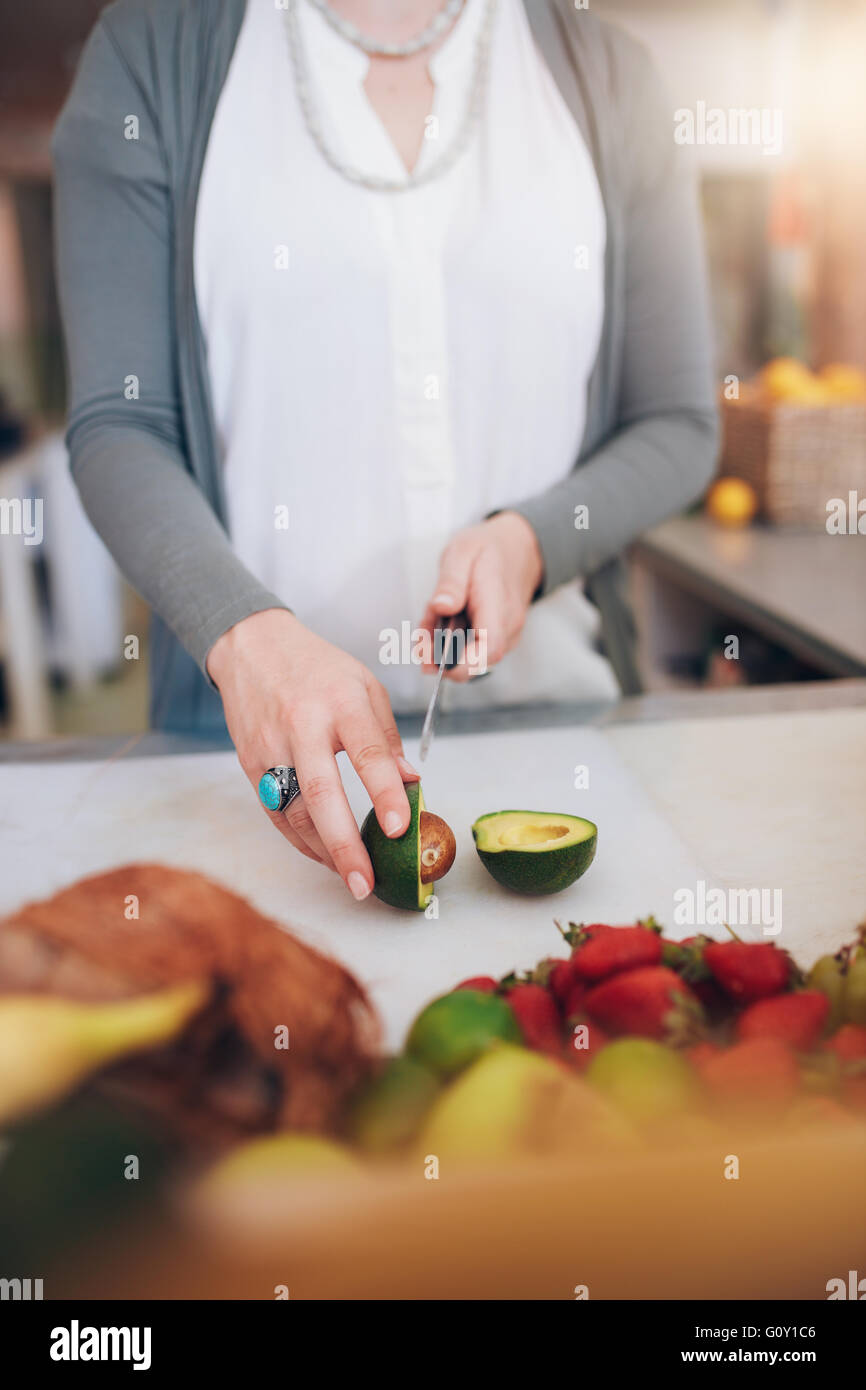 Cropped shot of woman cutting Avocado fruit at counter. Female working at juice bar. - Stock Image