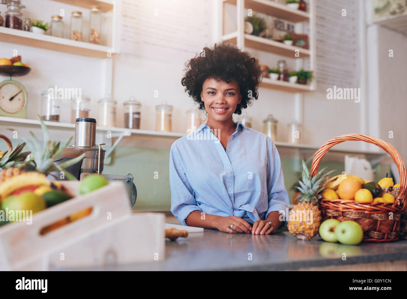 Portrait of beautiful young woman standing at counter in juice bar smiling to camera. African female juice bar owner. - Stock Image