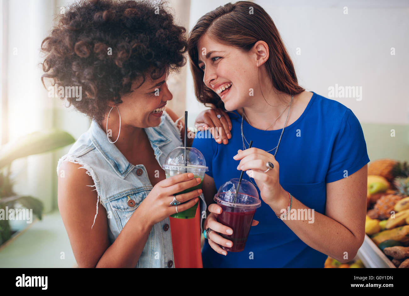 Portrait of cheerful young friends having fresh juice. Two young women at juice bar having a glass of fresh fruit - Stock Image