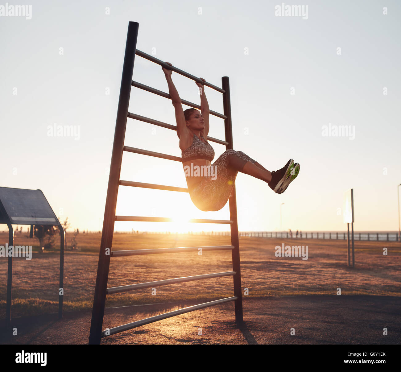 Full length shot of young woman exercising on wall bars with her legs up. Fitness woman exercising her abs with - Stock Image