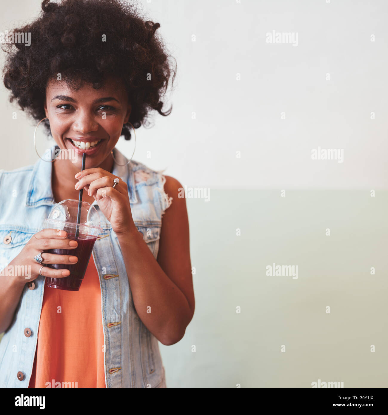 Portrait of happy young african woman having a fresh fruit juice. Young female model drinking juice with straw. - Stock Image