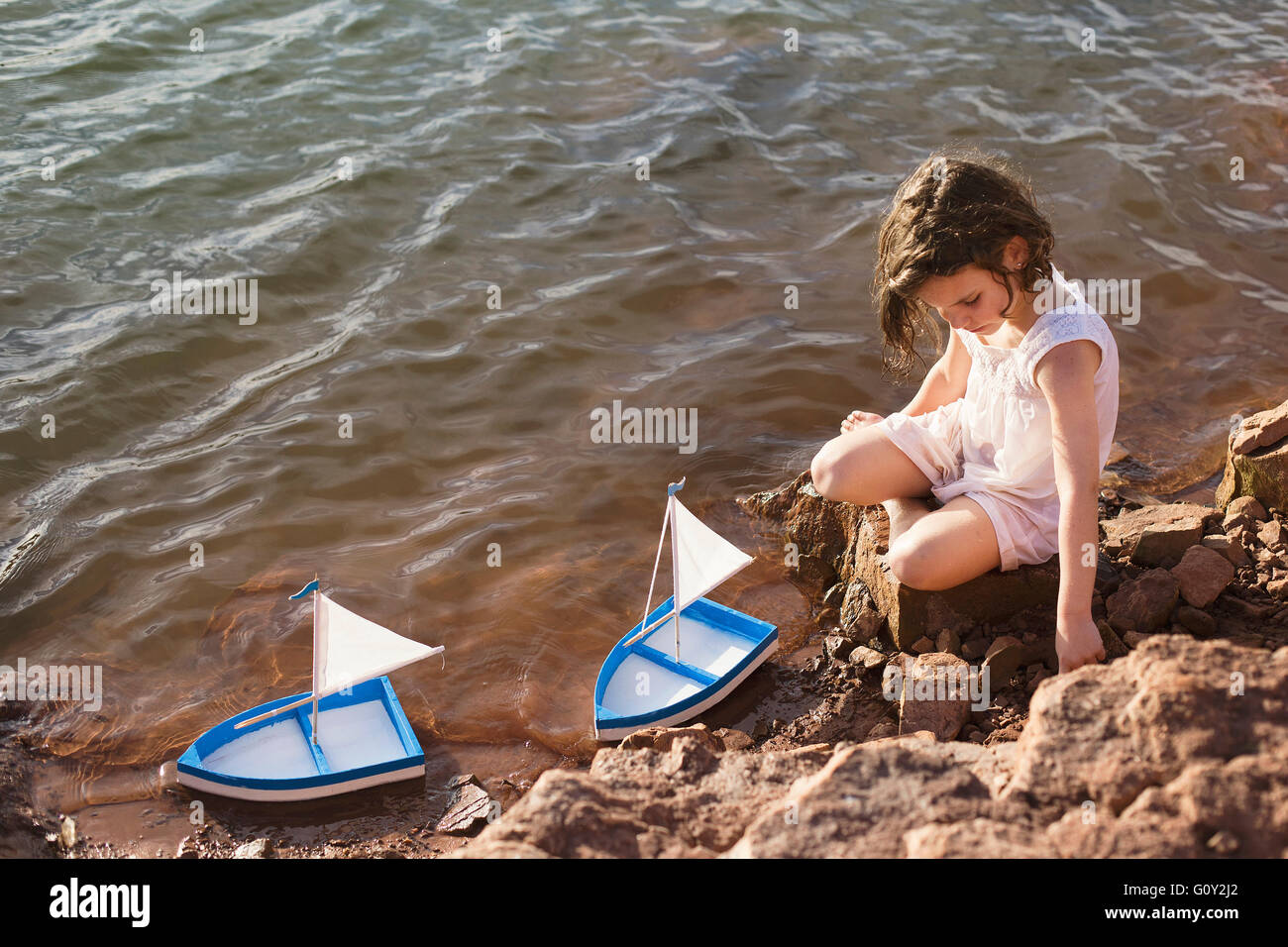 Girl sitting on rocks by lake playing with toy boats Stock Photo ...