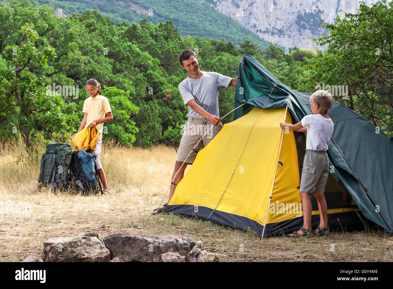 Father with children setting  tent - Stock Image