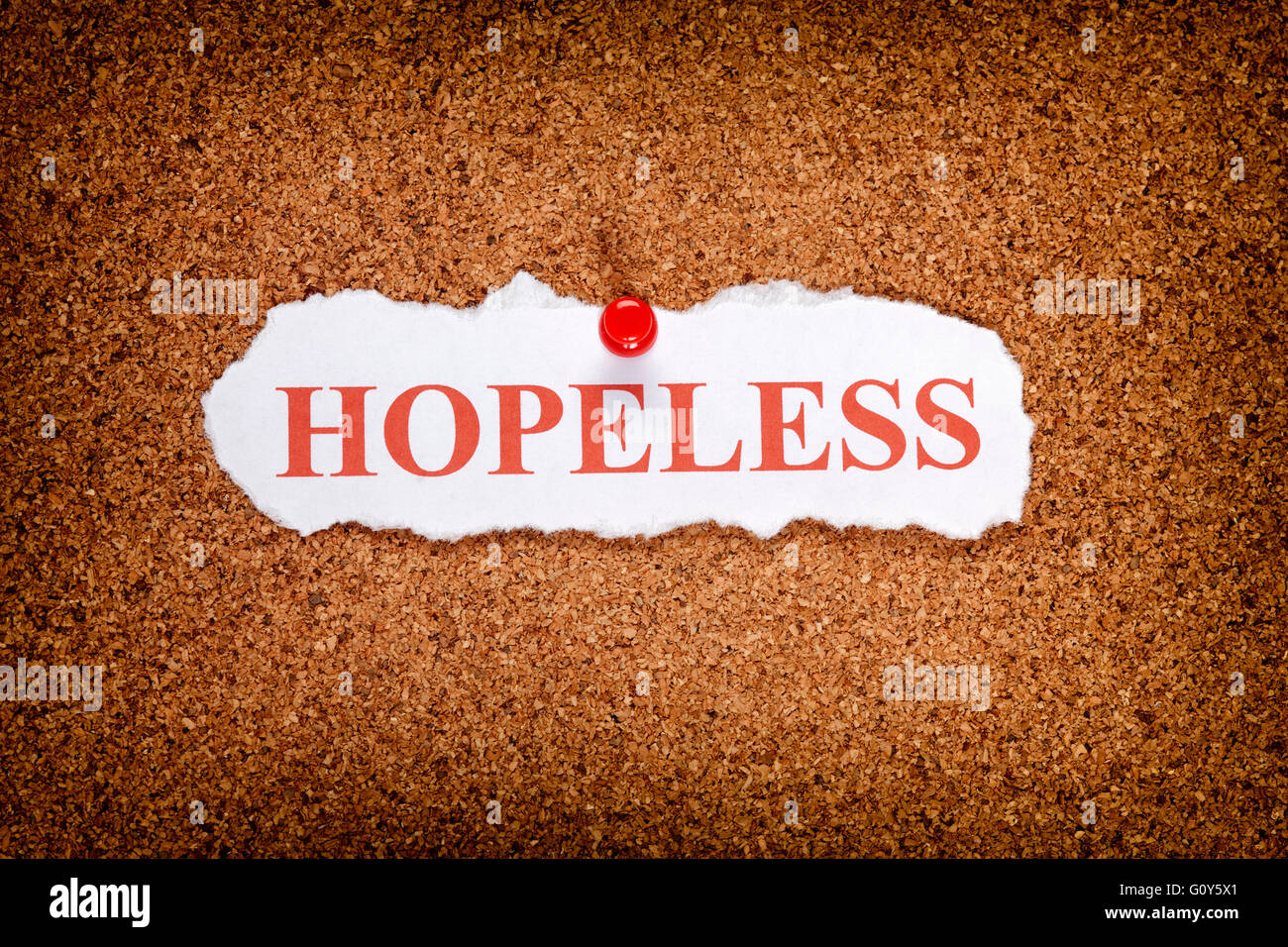 Torn piece of paper with word Hopeless. - Stock Image