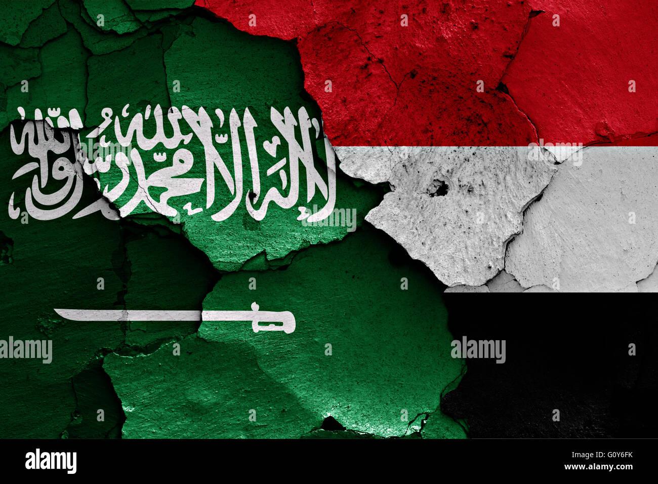 flags of Saudi Arabia and Yemen painted on cracked wall - Stock Image