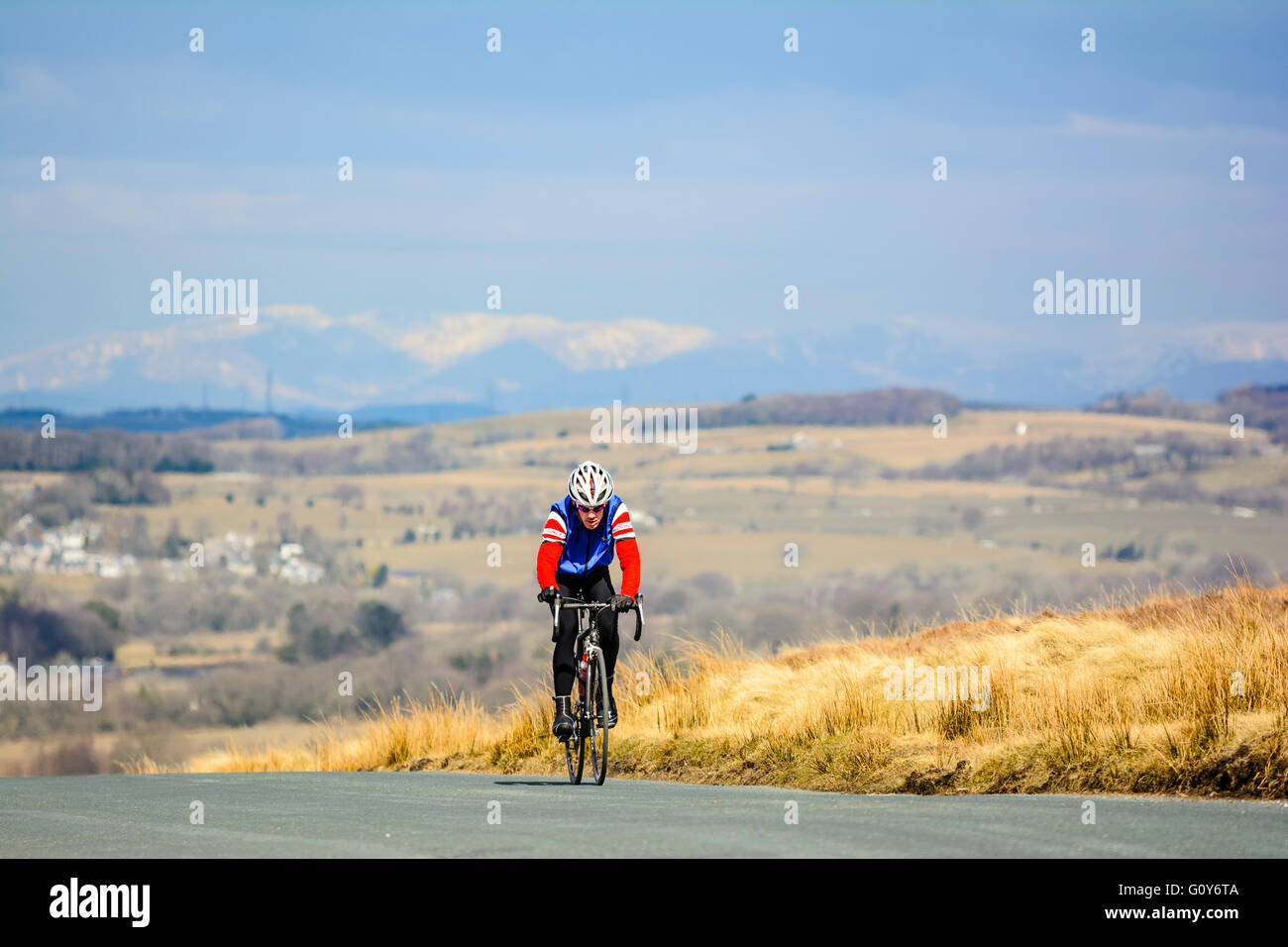 Cyclist on the climb of Harrisend Fell above Wyresdale Lancashire with the Lakeland Fells in the distance - Stock Image