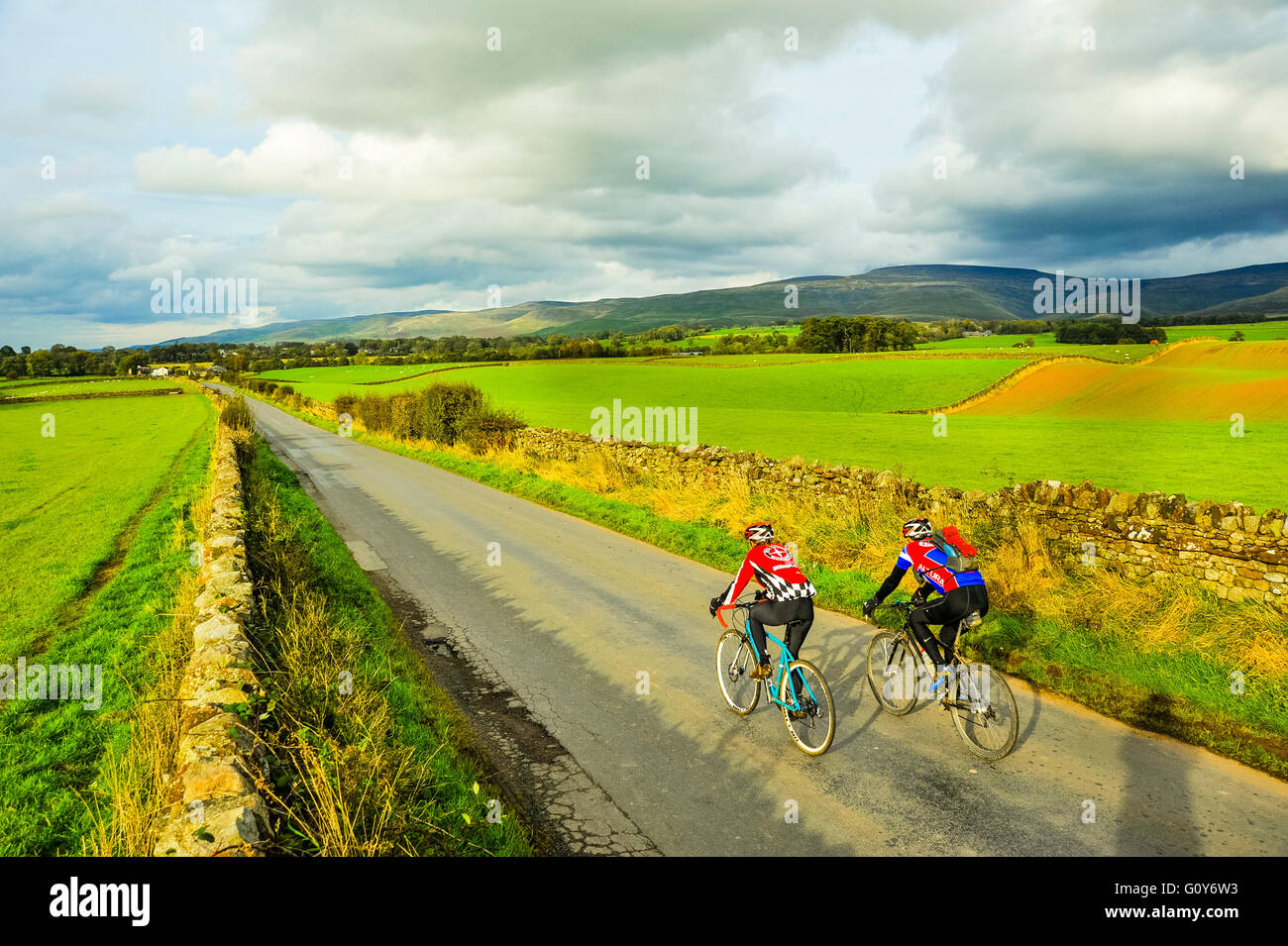 Cyclists on lane near Milburn in the Eden valley Cumbria with Cross Fell on the skyline - Stock Image