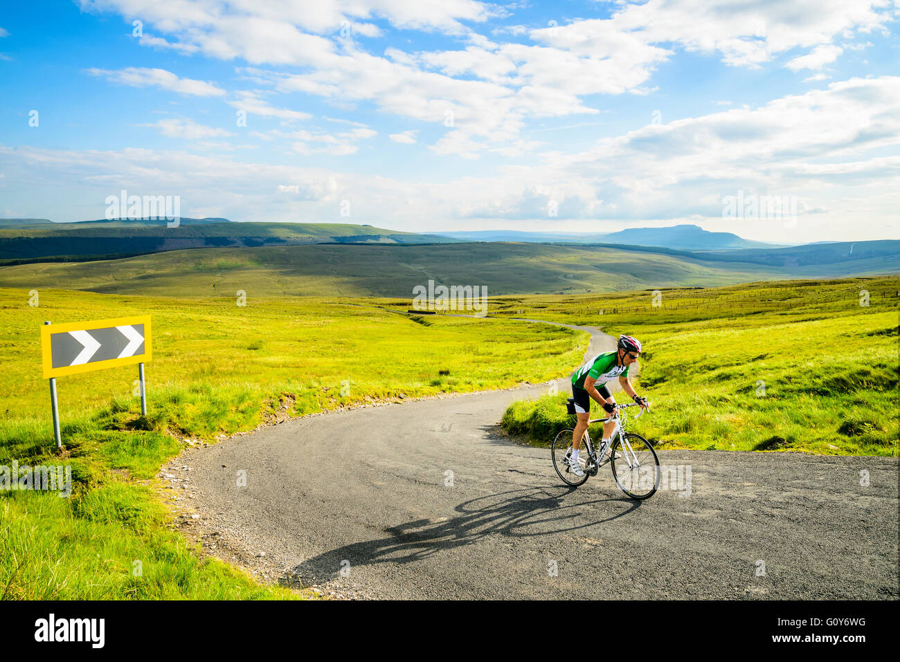 Cyclist near the top of Fleet Moss, the highest road in Yorkshire, with Ingleborough in the distance - Stock Image
