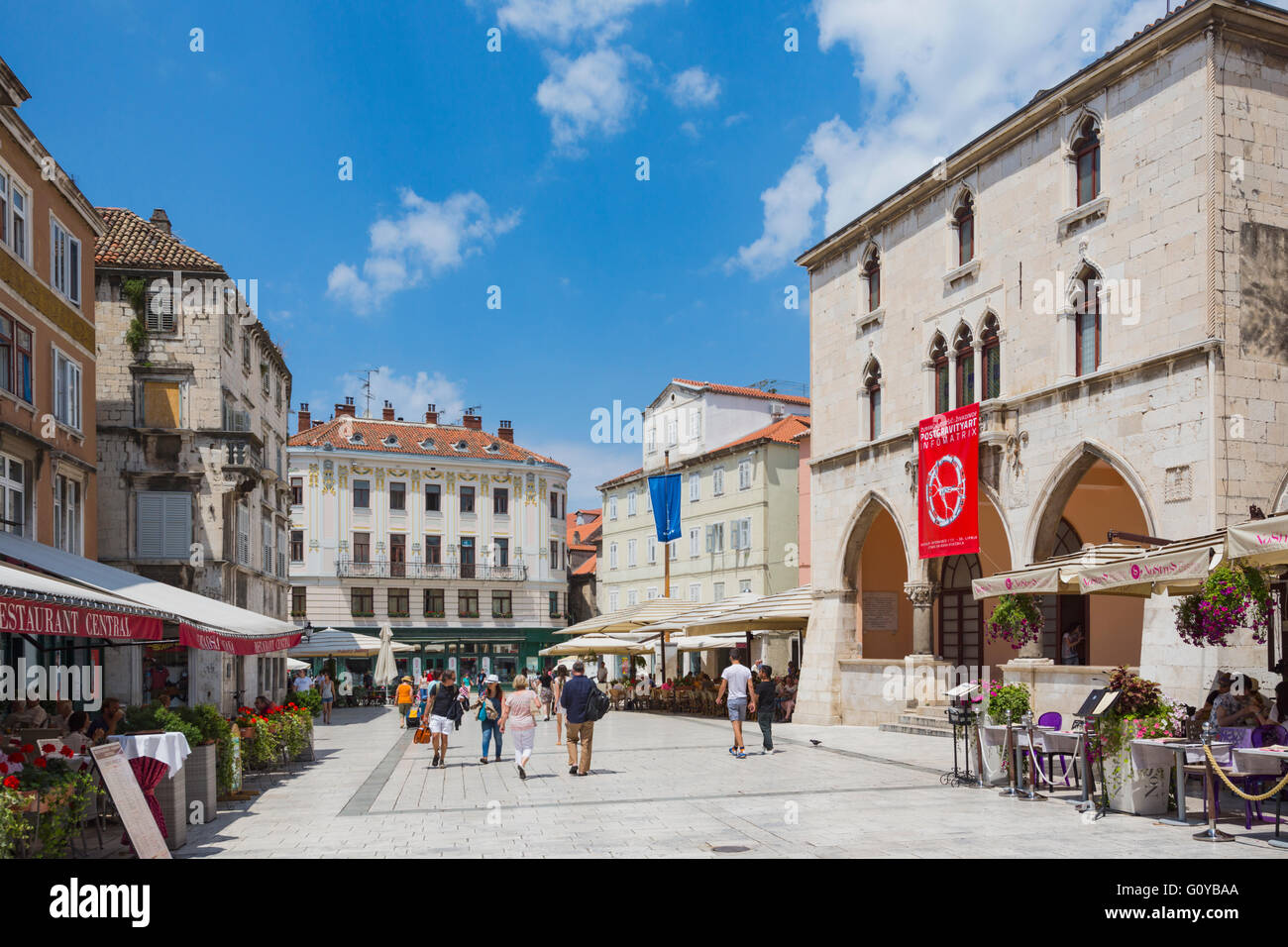 Split, Dalmatian Coast, Croatia.  People's Square.  The red banner hangs from the 15th century Renaissance Town - Stock Image
