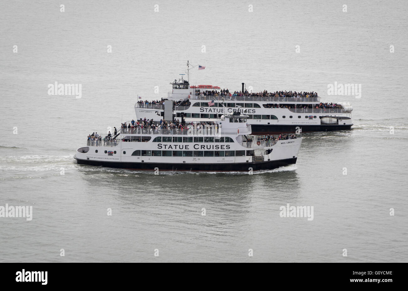 Two Statue Cruises ferry boats full of passengers passing on the Hudson River, New York City. - Stock Image