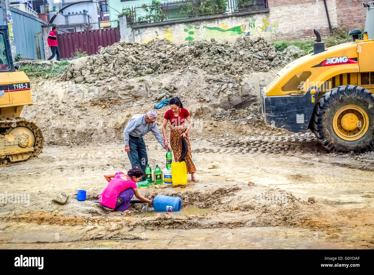 A local family takes water from a broken water line during the dry season in Kathmandu, one year after the 2015 - Stock Image